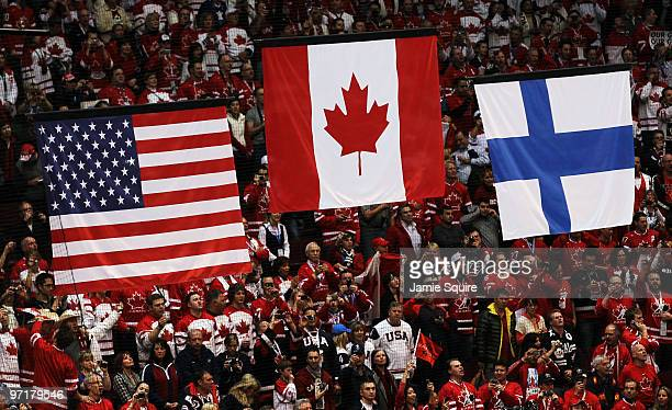 The flags of the United States Canada and Finland are raised during the medal ceremony after the ice hockey men's gold medal game between USA and...