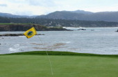 The flagstick on the 18th hole bends in the wind during a weather delay during the third round of the ATT Pebble Beach National ProAm at the Pebble...