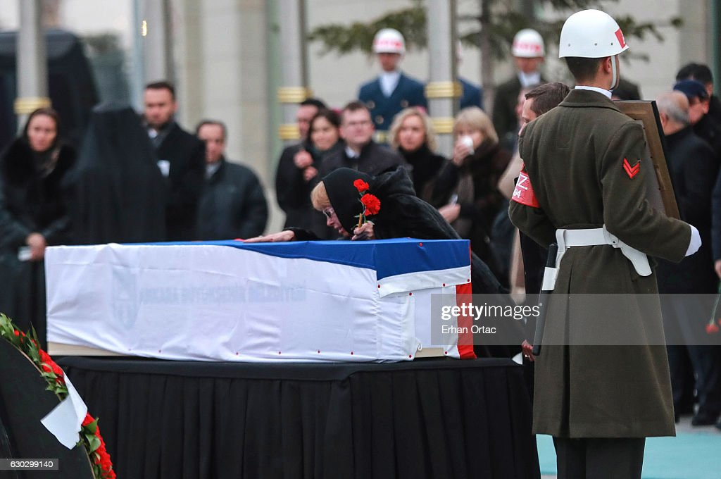 The flag-wrapped coffin of late Russian Ambassador to Turkey Andrei Karlov is carried to a plane by Turkish soldiers as his wife Marina mourns putting her hand on top of it during a ceremony at Esenboga airport on December 20, 2016 in Ankara. Turkey. Russia's ambassador to Turkey, Andrey Karlov, was shot dead by a Turkish policeman shouting 'Don't forget Aleppo! Don't forget Syria' at an art exhibition in the Turkish capital of Ankara yesterday.