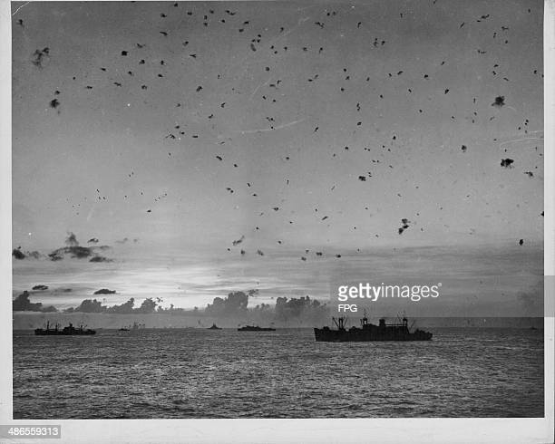 The flak from antiaircraft fire can be seen in the skies over US Coast Guard transport ships during the Pacific Campaign of World War Two Saipan...