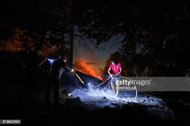 The flames near the road with volunteers and firefighters trying to put them out during a vast fire that threatened the areas inhabited between...