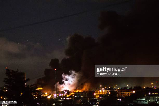 TOPSHOT The flash of an explosion is pictured amid flames and smoke billowing from the National Assembly building in Libreville after it was set...