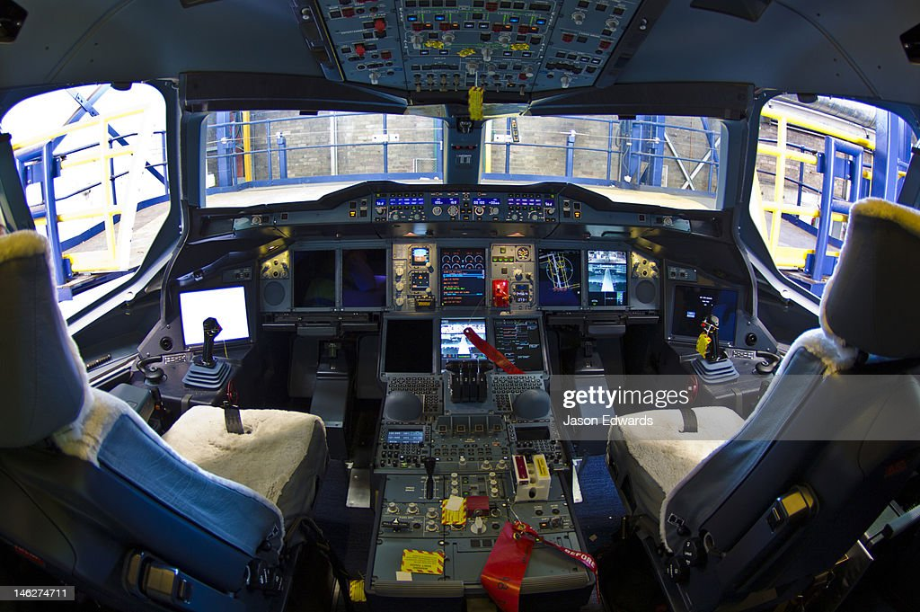 The flight controls and LED screens in the cockpit of a jet airliner. : Stock Photo