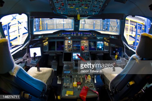 The flight controls and LED screens in the cockpit of a jet airliner.