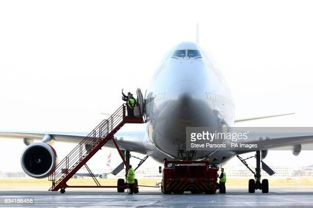 The flight crew of Virgin Atlantic's 747 wave to the media as the plane is pushed out of the Virgin Hanger at Heathrow Airport to take off to...