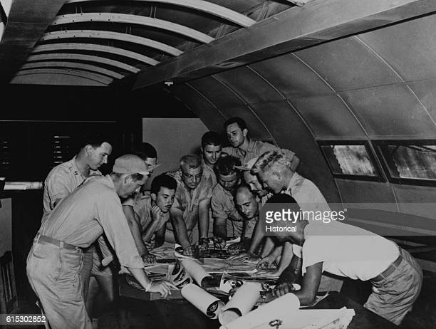 The flight crews of two planes go over planes for the dropping of the first atomic bombs The middleaged man in the center is Lt Col Payette On the...