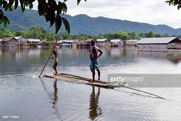 The flood affected people move towards high land for their life security on bamboo rafts in Kuthari village in Nagaon district About a hundred...