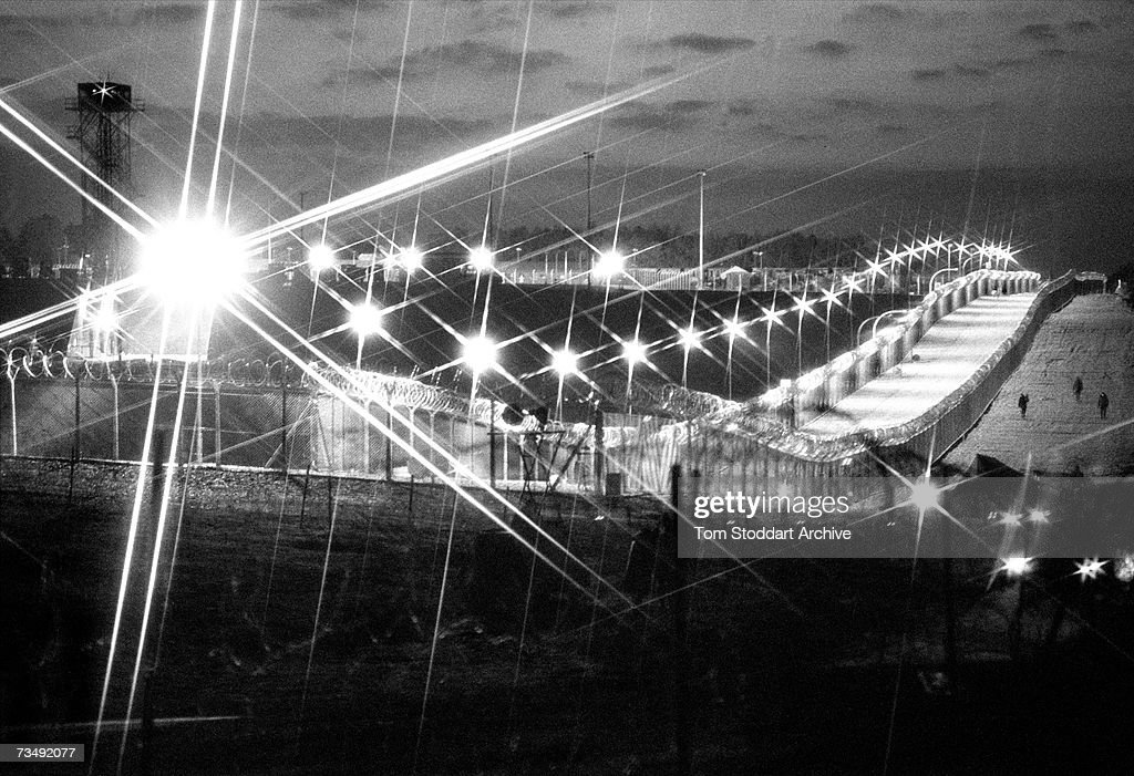 The floodlit Greenham Common air base near Newbury in Berkshire, where cruise missiles are stored after arriving from the USA, December 1983. Armed guards with dogs are used to patrol the barbed-wire perimeter fence to prevent entry by anti-nuclear campaigners opposed to the deployment of the nuclear missiles.