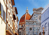 The Cathedral of Saint Mary of the Flower (Florence Cathedral) at historic center of Florence, Tuscany, Italy. View from the Piazza San Giovanni. Dome on blue sky background.