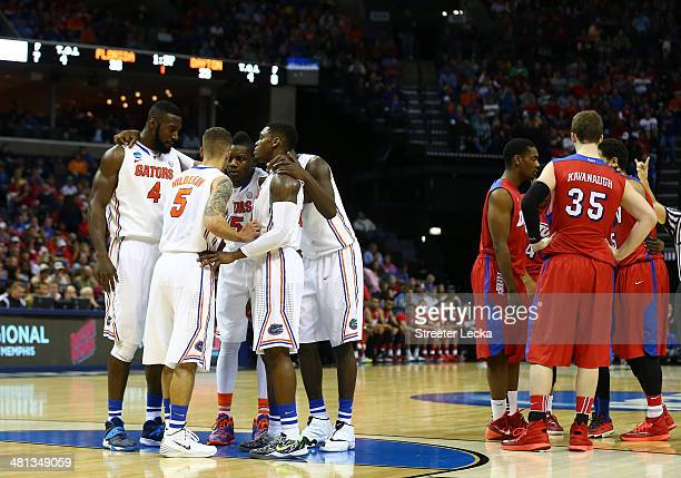 The Florida Gators and the Dayton Flyers huddle during the south regional final of the 2014 NCAA Men's Basketball Tournament at the FedExForum on...