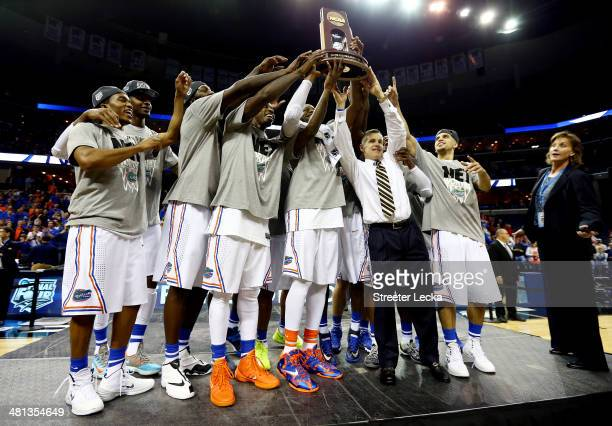 The Florida Gators celebrate with the trophy after defeating the Dayton Flyers 6252 in the south regional final of the 2014 NCAA Men's Basketball...