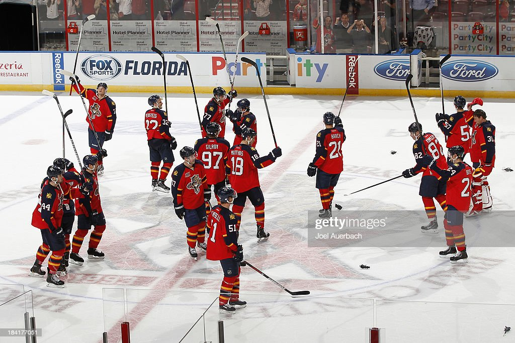 The Florida Panthers celebrate their victory against the Pittsburgh Penguins by raising their sticks at center ice and acknowledging the fans at the BB&T Center on October 11, 2013 in Sunrise, Florida. The Panthers defeated the Penguins 6-3.