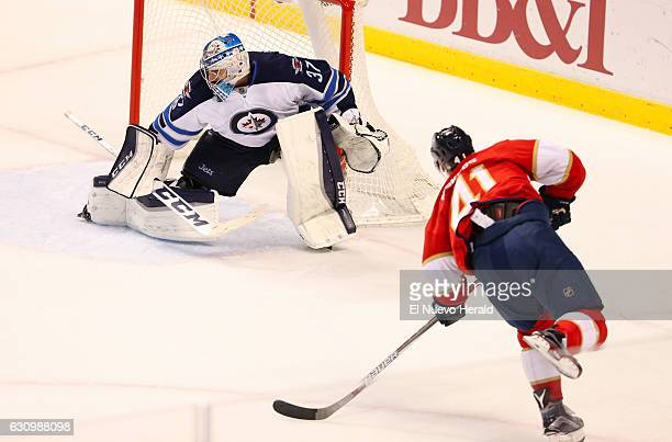 The Florida Panthers' Gregg McKegg scores a goal against Winnipeg Jets goalie Connor Hellebuyck during the second period at BBT Center in Sunrise Fla...