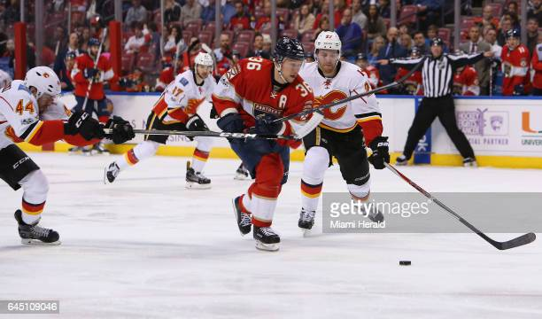 The Florida Panthers' Jussi Jokinen battles for the puck against the Calgary Flames' Dougie Hamilton and Matt Bartkowski during the second period at...