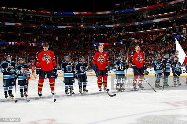 The Florida Panthers line up on the ice with junior skaters for the national anthem prior to the start of the game against the Buffalo Sabres at the...