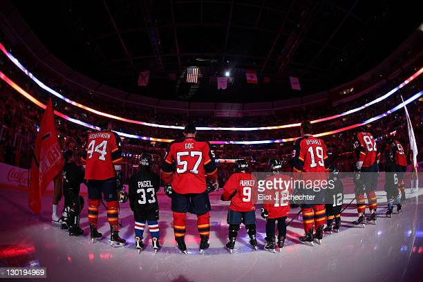 The Florida Panthers stand on the ice for the National Anthem with young skates prior to the start of the game against the New York Islanders at the...