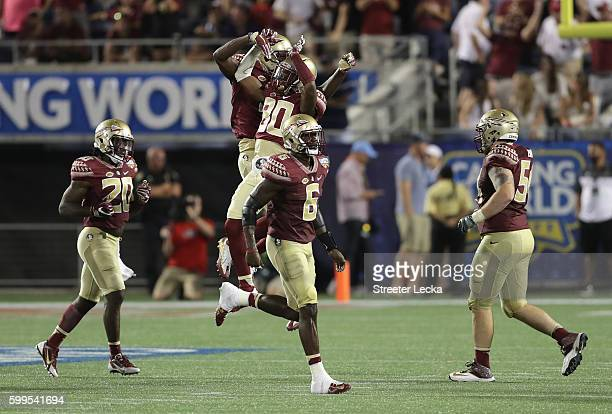The Florida State Seminoles celebrate after a fourth quarter interception by Tarvarus McFadden during the Camping World Kickoff against the...