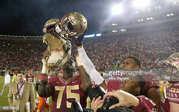 The Florida State Seminoles hold up a gator head after defeating the Florida Gators at Doak Campbell Stadium on November 29 2014 in Tallahassee...