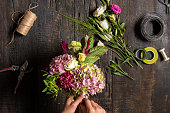 The hands of florist against desktop with working tools and ribbons on wooden background