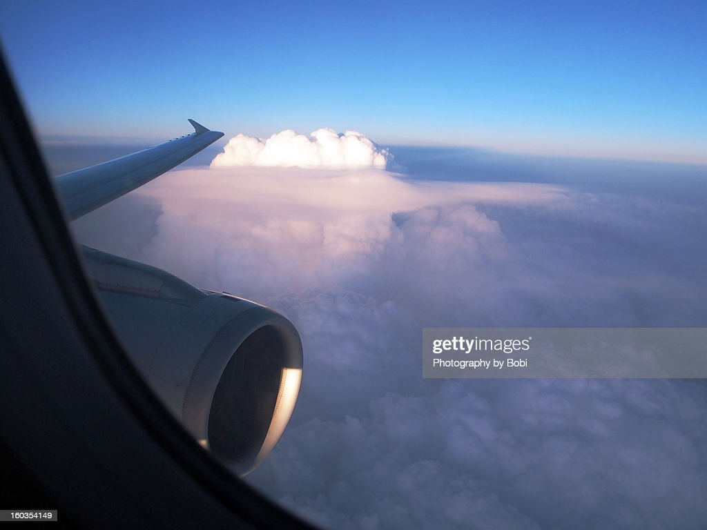 The flying aircraft in the sky and white clouds : Stock Photo