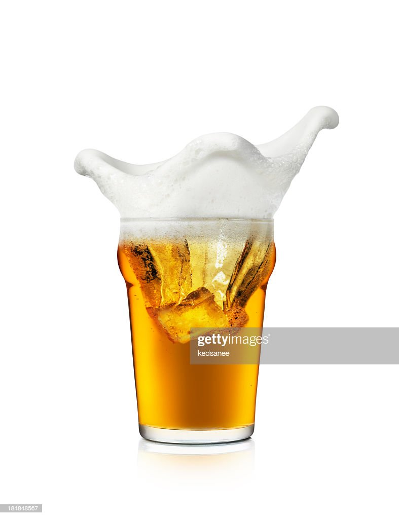 The foam on a glass of beer splashing the edges of the cup