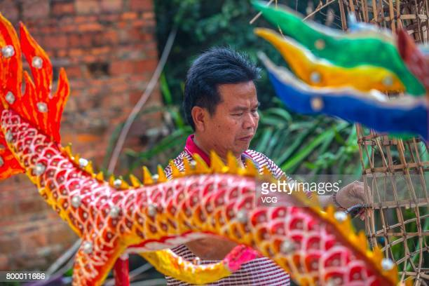 The folk artist Zhang Zijing bundles up a fire dragon with bamboo frames on June 19 2017 in Meizhou Guangdong Province of China The fire dragon dance...