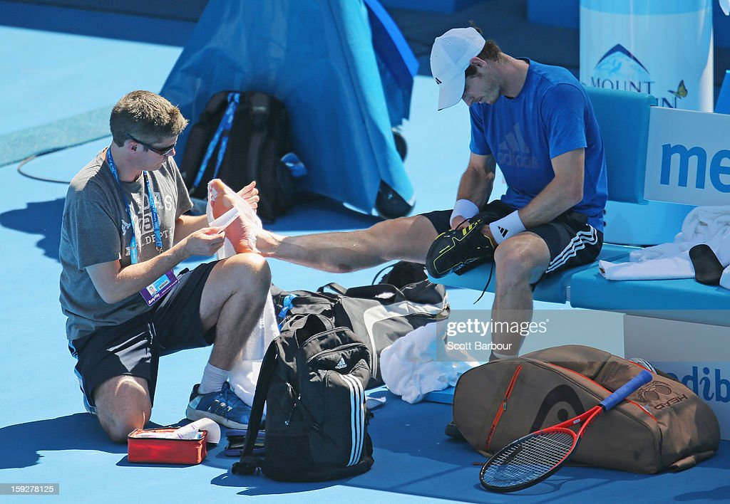 The foot of Andy Murray of Great Britain is attended to by a member of his support staff during a practice session ahead of the 2013 Australian Open at Melbourne Park on January 11, 2013 in Melbourne, Australia.