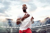 The football african player in motion on the field of stadium at day. The professional football, soccer player and human emotions concept. The win winner , victory concept