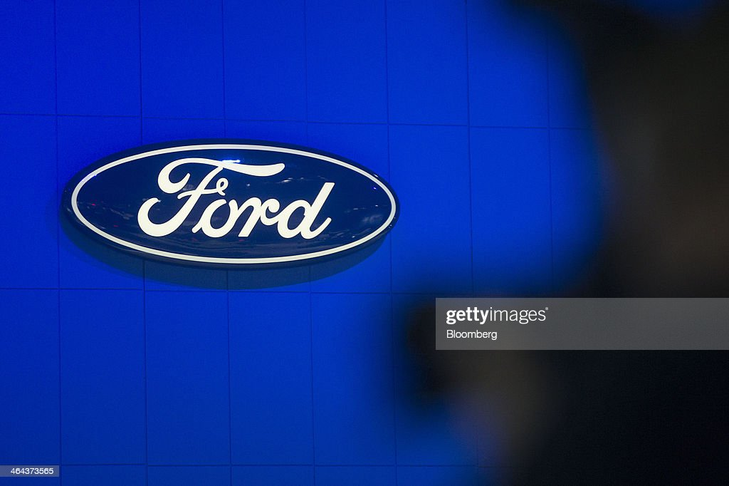 The Ford Motor Co. logo is seen past a photographer during the Washington Auto Show in Washington, D.C., U.S., on Wednesday, Jan. 22, 2014. After laboring for five years to develop its aluminum F-150, Ford Motor Co. now confronts a new challenge: preventing higher insurance rates and a dearth of mechanics equipped to repair its body from deterring buyers. Photographer: Andrew Harrer/Bloomberg via Getty Images