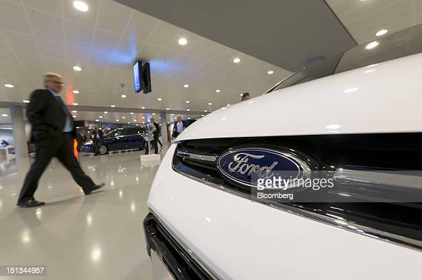 The Ford Motor Co logo sits on the hood of a new Ford CMax Titanium automobile as it stands on display during the company's 'Go Further' launch event...