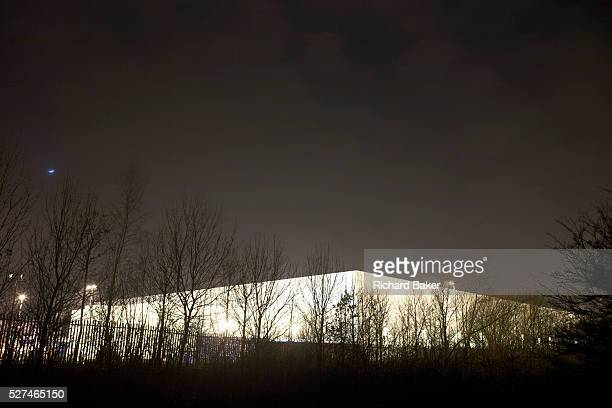 The form of a giant generic warehouse glows from ambient light at the DIRFT warehouse logistics park in Daventry Northamptonshire England Bare trees...