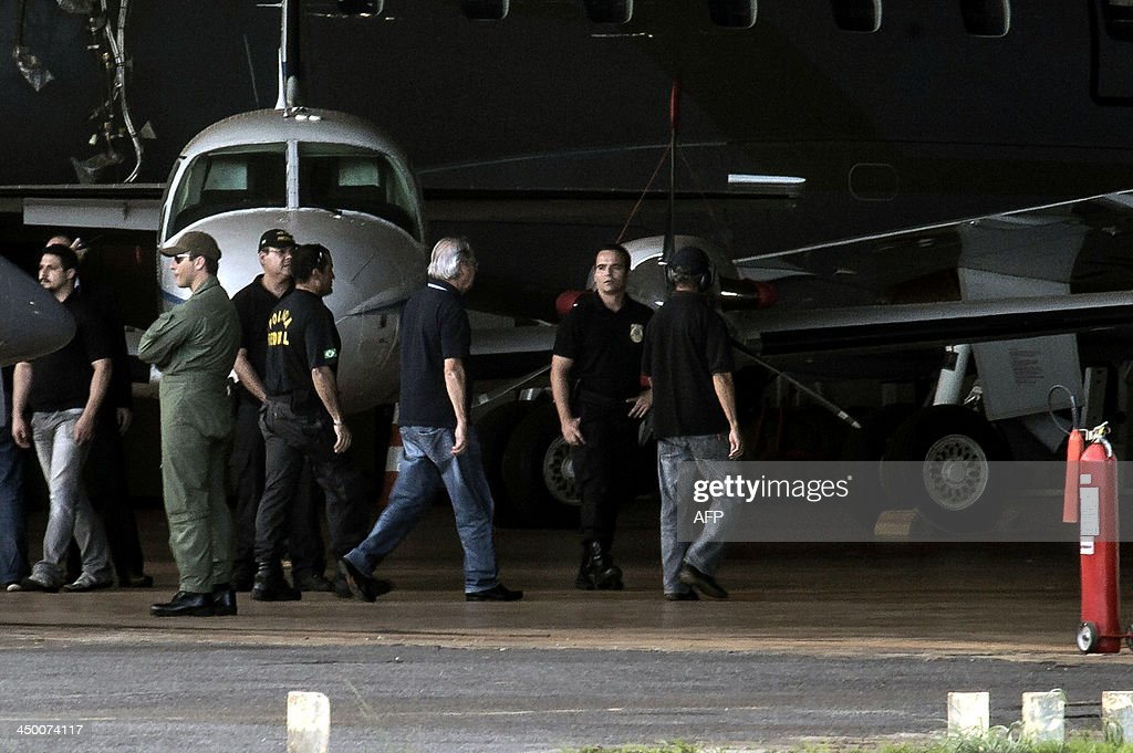 The former Chief of Staff of former Brazilian President Luiz Inacio Lula da Silva, Jose Dirceu (3rd-R), accused in the Mensalao scandal, arrives at the Federal Police Hangar in Brasilia on November 16, 2013. Several figures who recently wielded considerable political influence, including Genoino and Lula's former chief of staff Jose Dirceu, face detention under a semi-open regime. AFP PHOTO/Marcelo CASAL