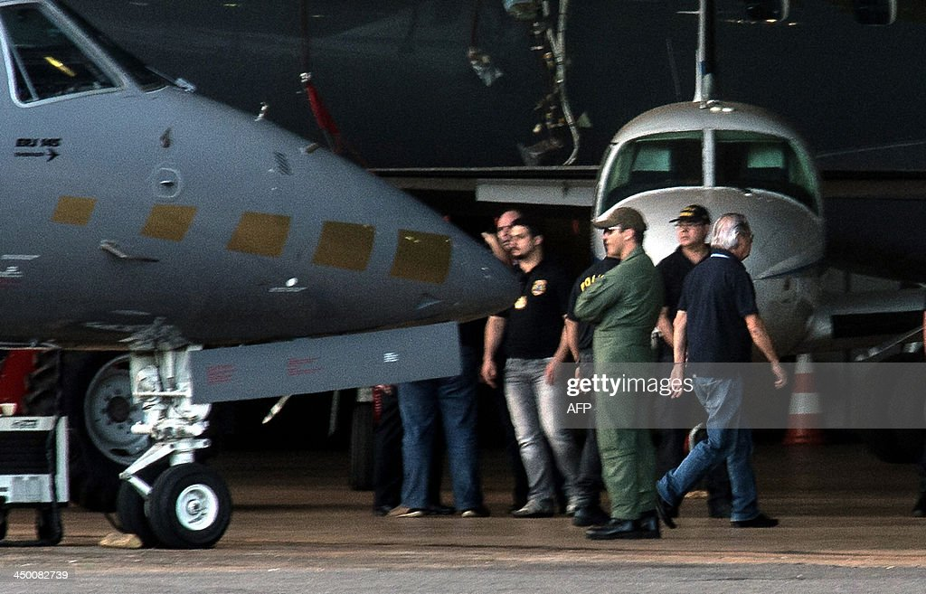 The former Chief of Staff of former Brazilian President Luiz Inacio Lula da Silva, Jose Dirceu (R), accused in the Mensalao scandal, arrives at the Federal Police Hangar in Brasilia on November 16, 2013. Several figures who recently wielded considerable political influence, including Dirceu, and the former president of the Workers Party (PT), Jose Genoino, face detention under a semi-open regime. AFP PHOTO/Marcelo CASAL