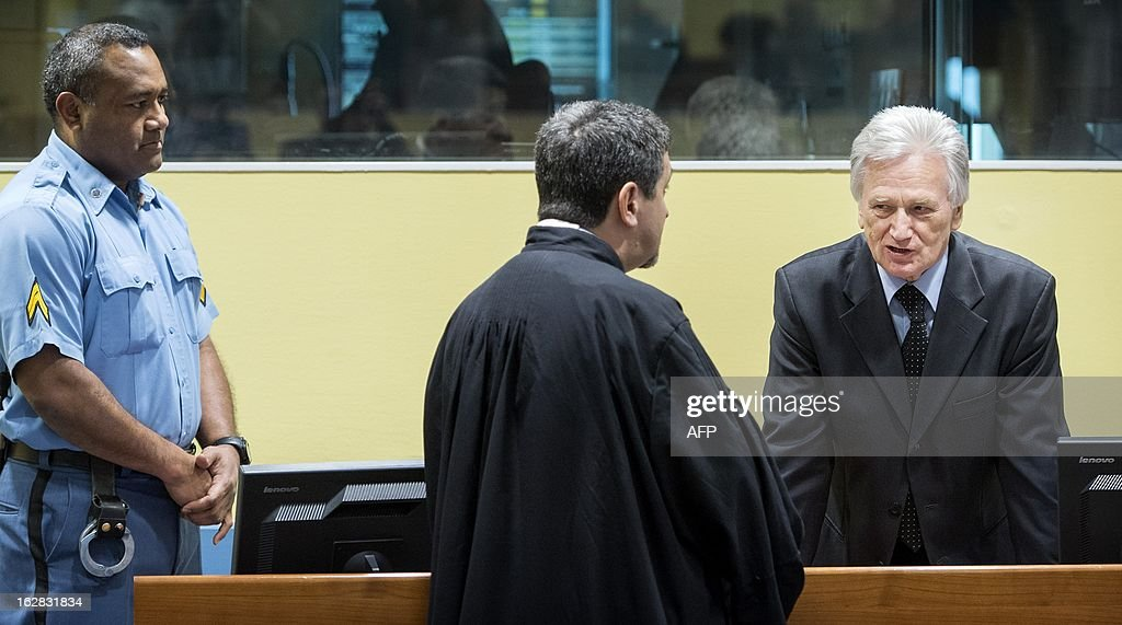 The former chief-of-staff of the Yugoslav Army, Momcilo Perisic (R), speaks on February 28, 2013 with a lawyer before his appeal judgement in a courtroom of the Yugoslav War Crimes Tribunal (ICTY) in The Hague. The UN war crimes court sentenced Perisic to 27 years in jail on Sepember 6, 2011 for helping the Bosnian Serb army murder and persecute Bosnian Muslims, including at Srebrenica in 1995.
