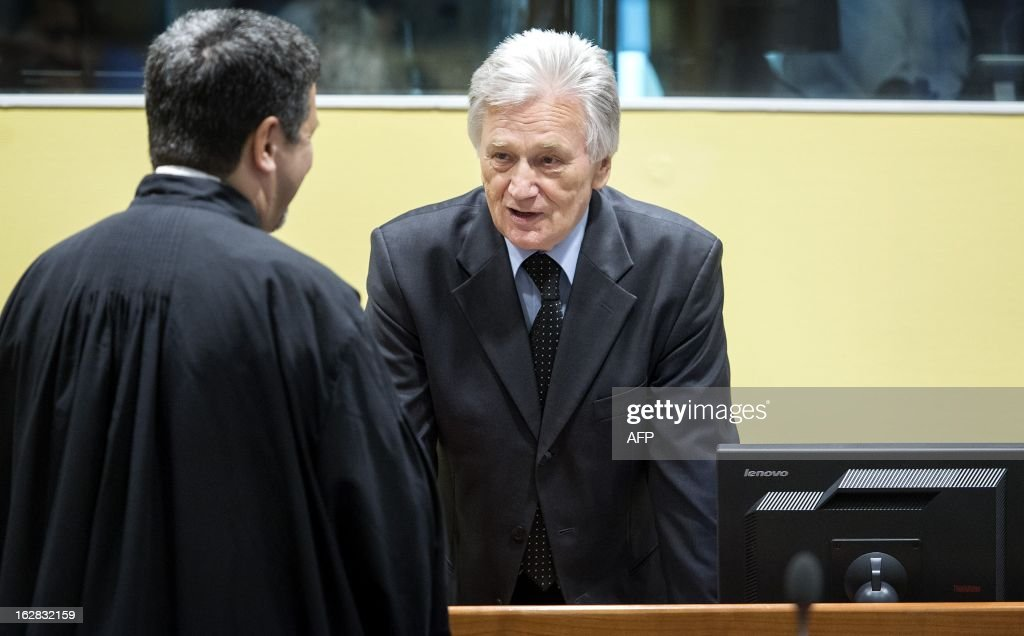 The former chief-of-staff of the Yugoslav Army, Momcilo Perisic (R), speaks on February 28, 2013 to a lawyer before his appeal judgement in a courtroom of the Yugoslav War Crimes Tribunal (ICTY) in The Hague. The UN war crimes court sentenced Perisic to 27 years in jail on Sepember 6, 2011 for helping the Bosnian Serb army murder and persecute Bosnian Muslims, including at Srebrenica in 1995. AFP PHOTO / POOL / KOEN VAN WEEL