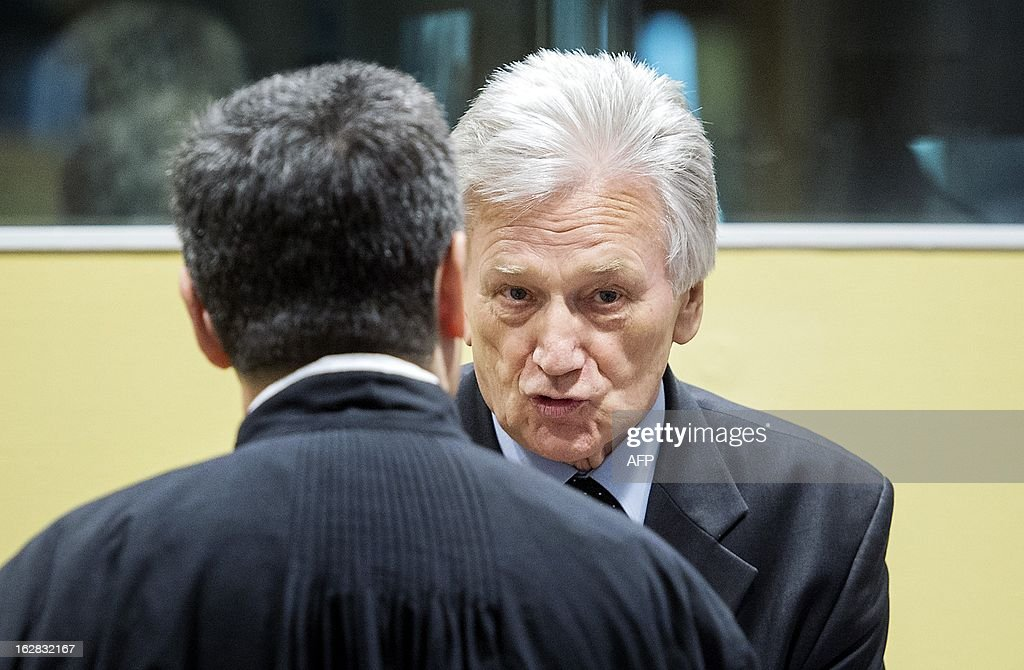 The former chief-of-staff of the Yugoslav Army, Momcilo Perisic (R), speaks on February 28, 2013 to a lawyer before his appeal judgement in a courtroom of the Yugoslav War Crimes Tribunal (ICTY) in The Hague. The UN war crimes court sentenced Perisic to 27 years in jail on Sepember 6, 2011 for helping the Bosnian Serb army murder and persecute Bosnian Muslims, including at Srebrenica in 1995.