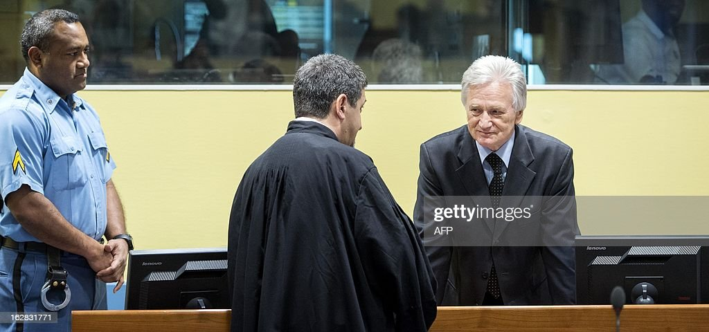 The former chief-of-staff of the Yugoslav Army, Momcilo Perisic (R), talks to a lawyer on February 28, 2013 before his appeal judgement in a courtroom of the Yugoslav War Crimes Tribunal (ICTY) in The Hague. The UN war crimes court sentenced Perisic to 27 years in jail on Sepember 6, 2011 for helping the Bosnian Serb army murder and persecute Bosnian Muslims, including at Srebrenica in 1995.