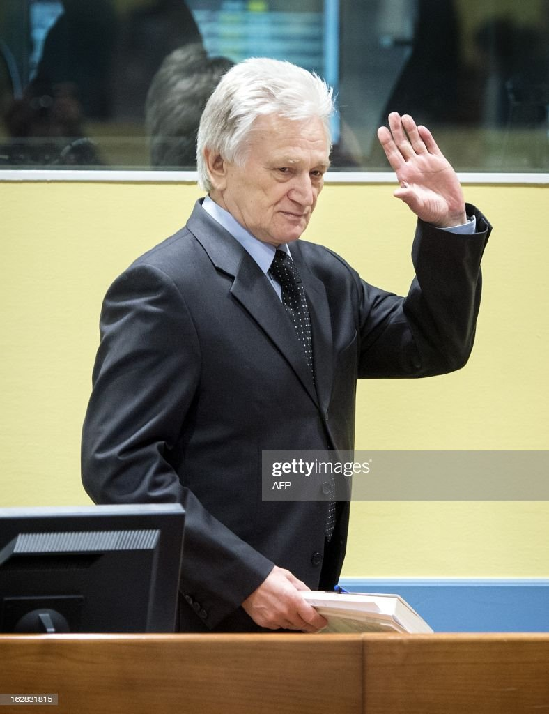 The former chief-of-staff of the Yugoslav Army, Momcilo Perisic, waves on February 28, 2013 as he arrives for his appeal judgement in a courtroom of the Yugoslav War Crimes Tribunal (ICTY) in The Hague. The UN war crimes court sentenced Perisic to 27 years in jail on Sepember 6, 2011 for helping the Bosnian Serb army murder and persecute Bosnian Muslims, including at Srebrenica in 1995.