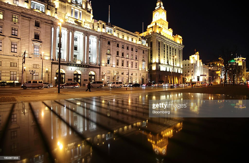 The former HSBC headquarters building, which now houses Shanghai Pudong Development Bank Co., left, and the Customs House, second left, stand with other historical buildings illuminated on the Bund at night in Shanghai, China, on Monday, Jan. 28, 2013. China's economic growth accelerated for the first time in two years as government efforts to revive demand drove a rebound in industrial output, retail sales and the housing market. Photographer: Tomohiro Ohsumi/Bloomberg via Getty Images