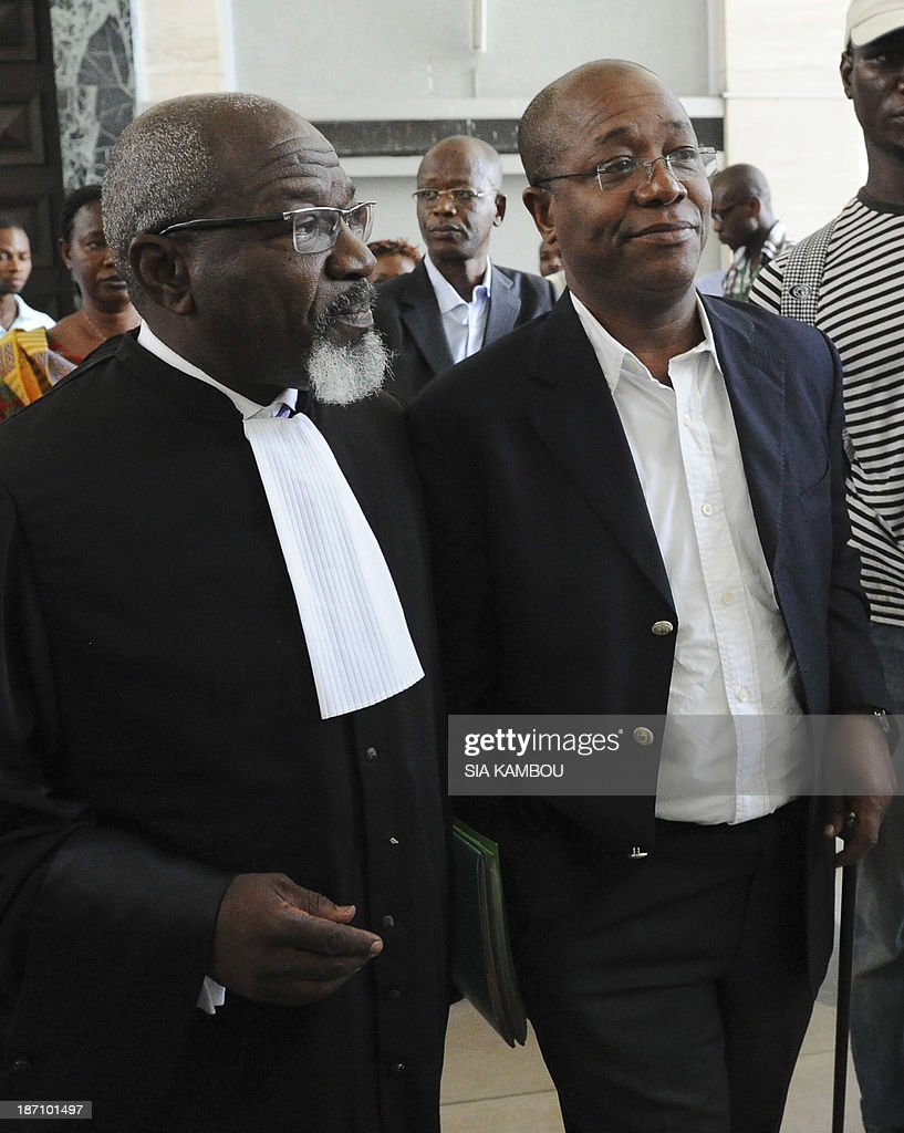 The former managing director of the Ivorian cocoa farmers development fund, Henri Amouzou (R), leaves on November 6, 2013 the Abidjan tribunal with his lawyer after being sentenced to 20 years in jail for misappropriation of corporate assets. Ivory Coast, the worlds biggest cocoa grower, sentenced 14 former managers of state-run cocoa agencies to 20 years in prison following the nations biggest probe into corruption in the industry. The defendants were found guilty of charges including misappropriation of corporate assets, embezzlement of public funds, breach of trust and fraud, Presiding Judge Hamed Coulibaly said.