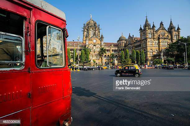 The former Victoria Terminus Railway Station now Chhatrapati Shivaji Terminus seen across the square with a red bus crossing