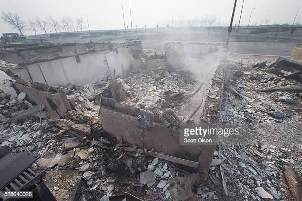 The foundation of a home smolders in a residential neighborhood destroyed by a wildfire on May 6 2016 in Fort McMurray Alberta Canada Wildfires which...