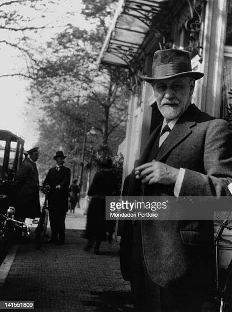 The founder of psychoanalysis Sigmund Freud smoking a cigar on the footpath of a city street Austria 1920