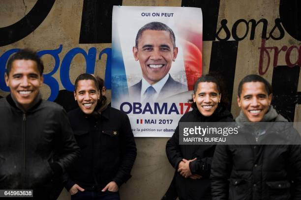 The four authors of 'Obama 17' pose in front of a poster to promote Obama's candidacy to the French presidential election in 2017 on February 27 2017...