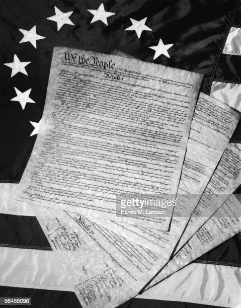 The four pages which comprise the United States Consitution lie spread out on an American flag of a Colonial Era design late 20th Century