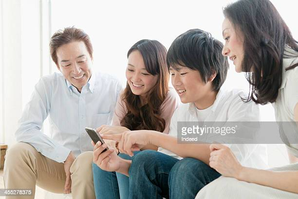 The four-person family surrounding a smart phone