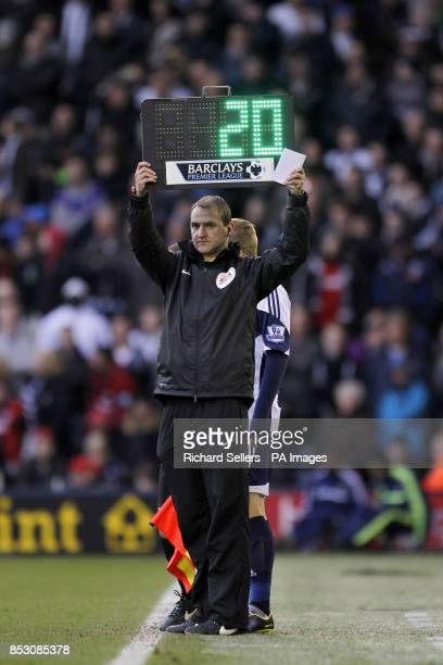 The fourth official holds up a substitutes board to bring on a player