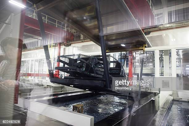 The frame of a Honda Motor Co 2017 Acura NSX vehicle is lowered into coating material at the Honda Performance Manufacturing Center in Marysville...