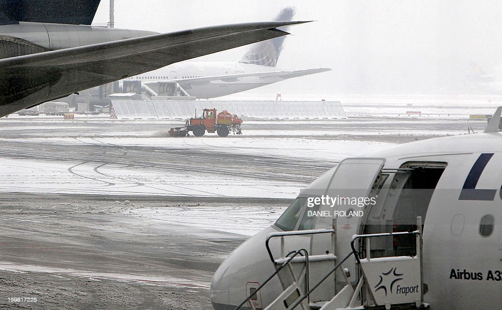 The Frankfurt am Main airport's snowcovered ground is cleaned next to airplanes on January 21, 2013 as more than 200 flights were cancelled at Germany's busiest airport due to heavy snowfall. ROLAND