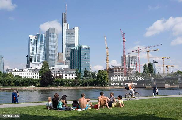 The Frankfurt Skyline with construction cranes Young people picnicking on the river Main on July 25 2014 in Frankfurt Germany